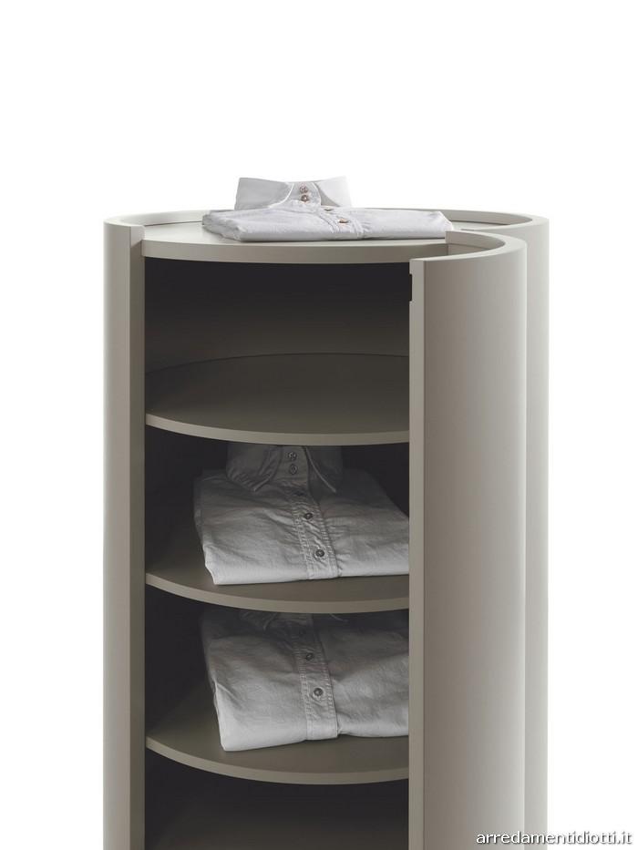 L'apertura del frontale curvo consente di accedere agevolmente al suo interno, organizzato a ripiani.  Il top si inserisce con un effetto a vassoio nel quale trovano ospitalità oggetti di uso quotidiano.