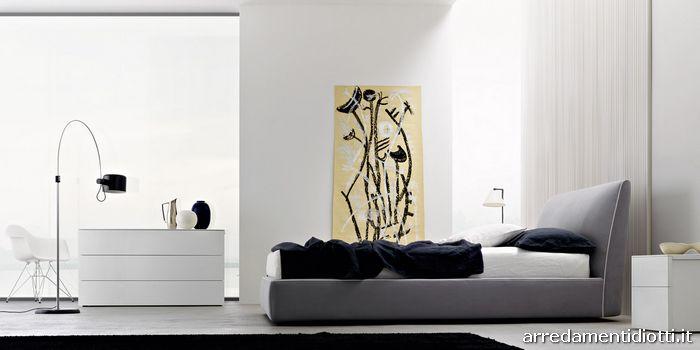 Letto Atelier rivestito in tessuto grigio chiaro con bordino bianco a contrasto.  I comodini Sosia sono in rovere laccato bianco