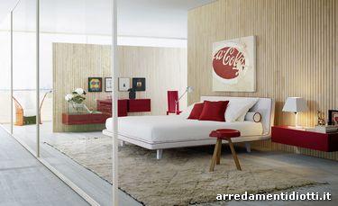 Letto Zenit con rivestimento in tessuto bianco con bordino in tessuto rosso. Cuscini rossi e bianchi con bordini in tinta e rullo con bordino a contrasto