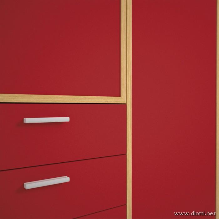 Il profilo-cornice in massello di rovere sbiancato di un'anta dell'armadio contrasta con i pannelli in finitura laccato rosso.