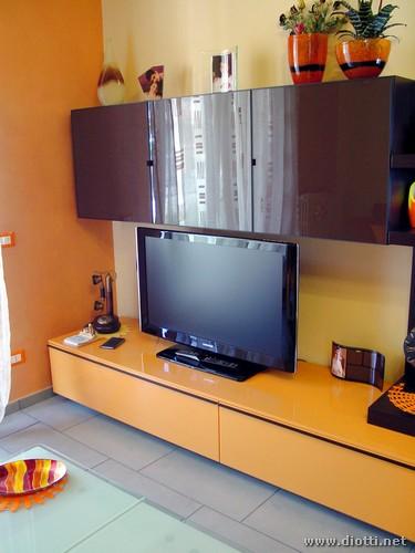 La base porta tv arancio del soggiorno Day, con i pensili in cristallo visone con telaio alluminio in tinta.