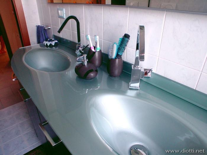 Il miscelatore in acciaio cromato fa da accento per ognuna delle 2 vasche del piano in cristallo.