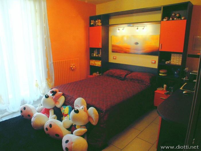 La camera matrimoniale Young in rovere tinto wengè e laccato arancio opaco, con una struttura retro-letto su misura.