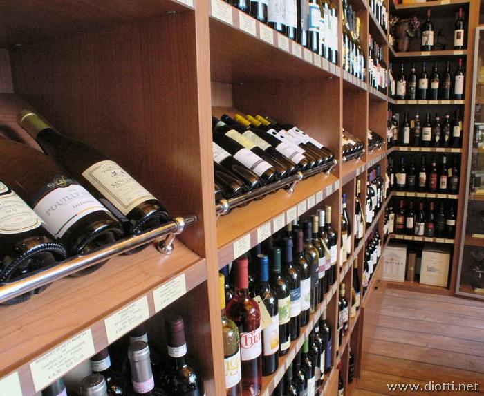 Bel particolare dei ripiani speciali inclinati per accogliere le bottiglie, con barre cromate per fermare e valorizzarle.